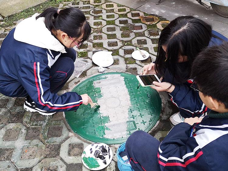 初二学生正在井盖上作画-(1).jpg