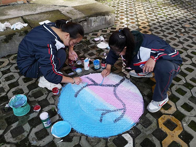初二学生正在井盖上作画-(11).jpg