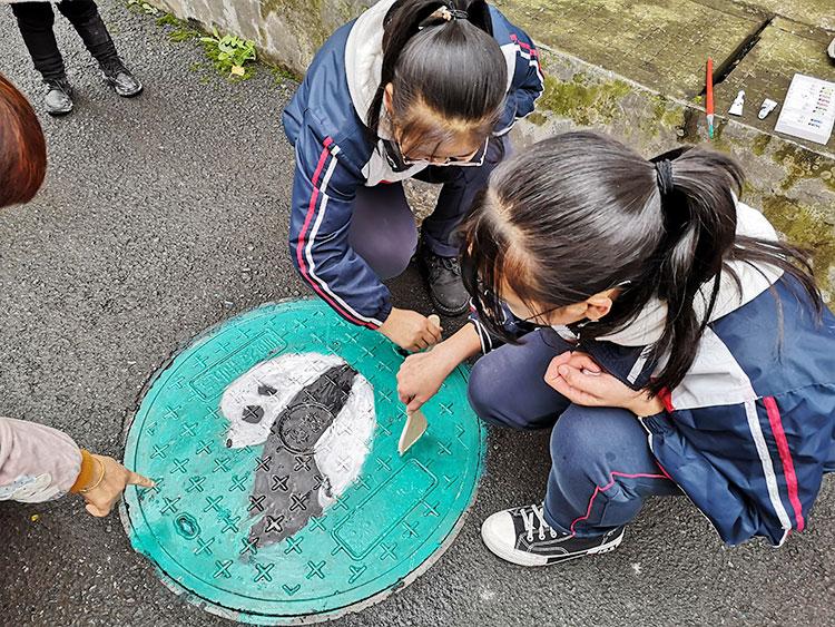 初二学生正在井盖上作画.jpg
